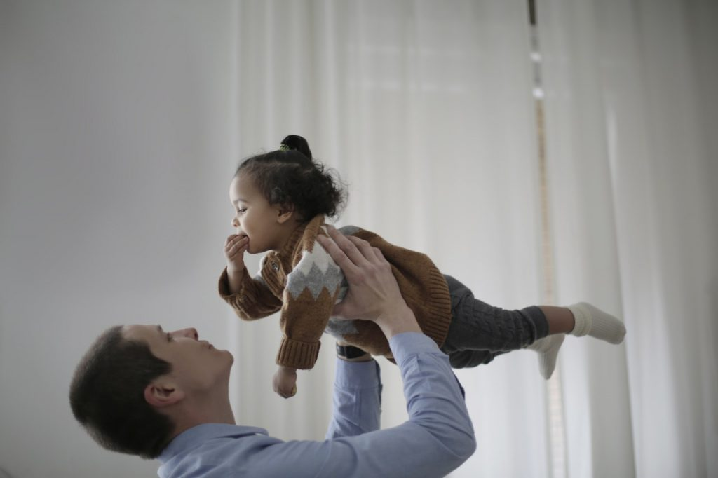 baby playing with father